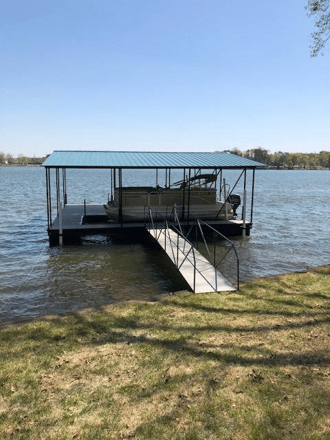 Double slip steel floating dock with wide side toward lake. 20' walkway.